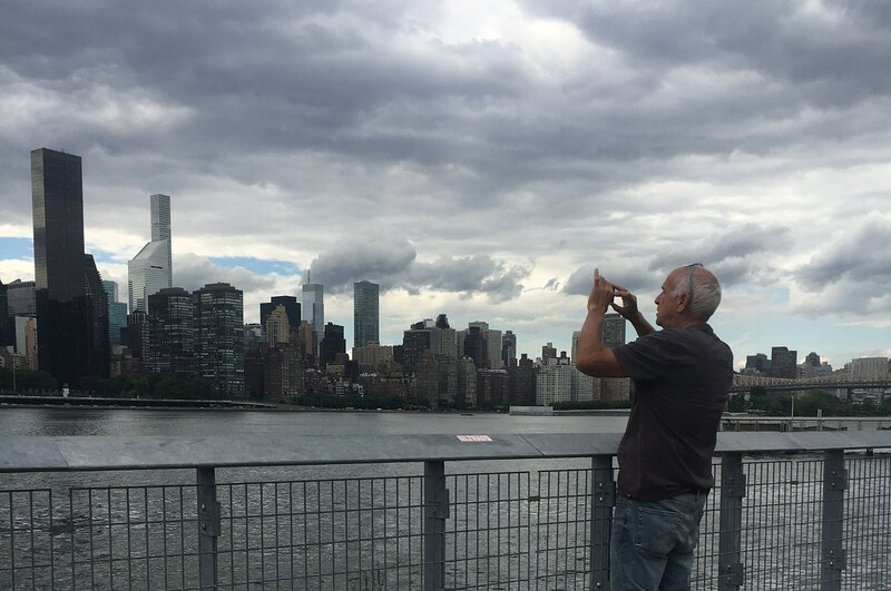 An image of a man taking a picture of the Manhattan skyline from Hunter's Point South Park