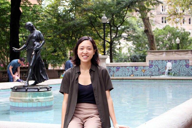 Christine Chung sits on the edge of a fountain