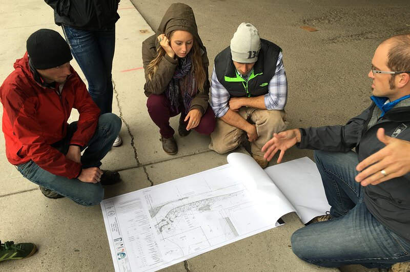 Students gather around a siteplan
