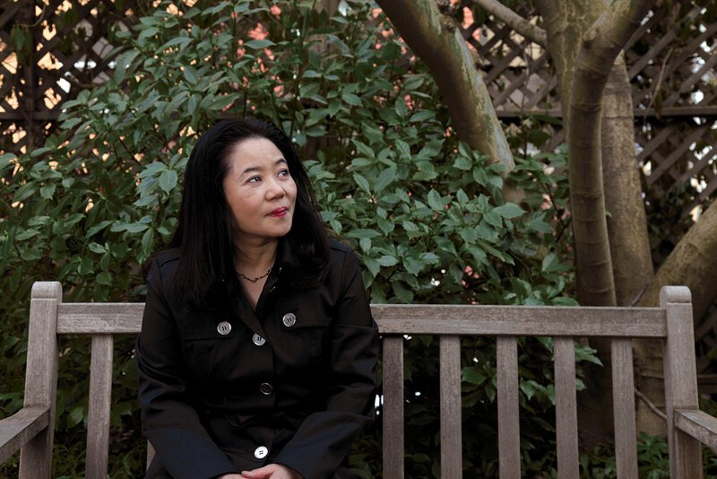 A portrait of Noriko Maeda seated on a bench