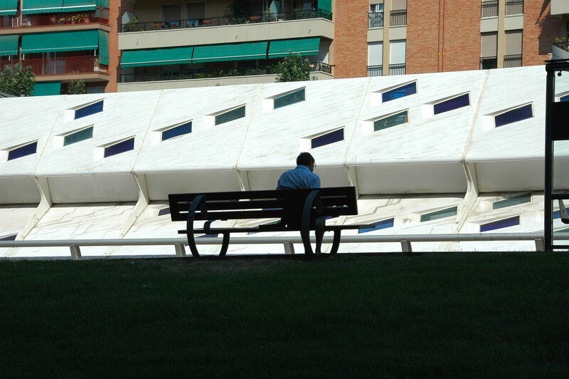 David Malda sits on a bench in shadow. Farther away, there is a brightly lit white angular wall.