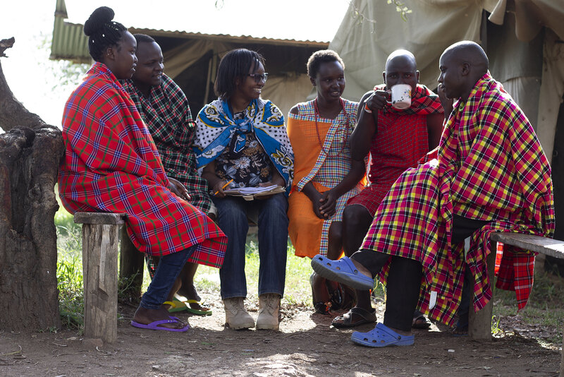 2019 CSI research assistant Carolyne Wanza Nthiwa sits and talks with Maasai community members on wooden benches