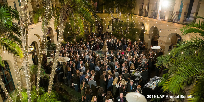 Hundreds of guests mingle in a courtyard framed by palm trees at the 2019 LAF Annual Benefit