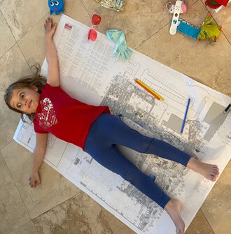 A young girl lays on top of a landscape architecture planting plan drawing.