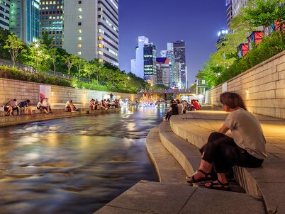 People sit by the restored Cheonggyecheon Stream in Seoul at night