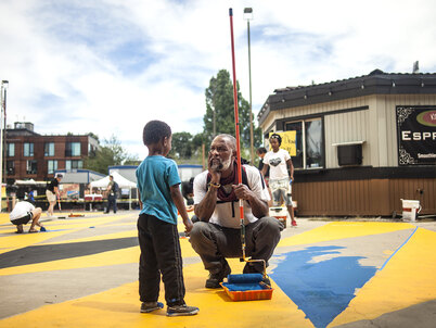 An older man holding a paint roller on a long handle squats down to take a break from painting blue triangles on the pavement to talk with a young boy