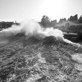 Waves crash over a breakwall near a road and buildings