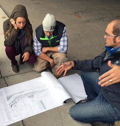 An instructor gestures toward a siteplan as students look on