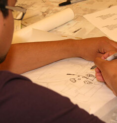 A landscape architecture student draws on trace paper