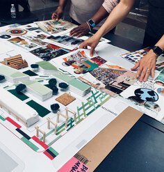 A project model sits on a table while many hands flip through pages of magazines and other colorful paper to add