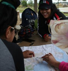 Hispanic/Latino youth gather around a map at a picnic table