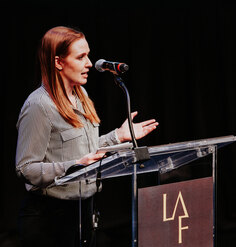 Lauren Delbridge presents at a podium emblazoned with the LAF logo