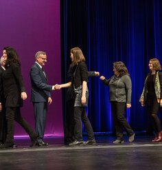 LAF staff walk across the stage to receive an Honor Award in Research